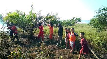 Sejumlah bocah yang ikut membantu Manggala Agni memadamkan kebakaran lahan gambut.(Liputan6.com/Ahmad Akbar Fua)