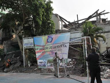 Guru memindahkan gawang di dekat bangunan yang ambruk di SMP Negeri 32, Pejagalan, Tambora, Jakarta, Selasa (14/8).  Setelah ambruk pada akhir tahun lalu gedung SMPN 32 kini sangat memprihatinkan.(Merdeka.com/ Iqbal S. Nugroho)