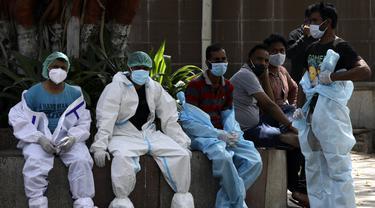 Petugas kesehatan beristirahat saat sela-sela mengkremasi korban COVID-19 di New Delhi, India, Senin (19/4/2021). New Delhi memberlakukan lockdown selama seminggu untuk mencegah runtuhnya sistem kesehatan di tengah ledakan kasus COVID-19. (AP Photo/Manish Swarup)
