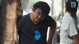 Seorang warga membasuh wajahnya usai mengalami mata perih saat melintas di Jalan KS Tubun, Petamburan, Jakarta Barat, Kamis (23/5/2019). Sisa gas air mata untuk membubarkan massa dalam kericuhan aksi 22 Mei masih terasa dan mengganggu aktvitas pengguna jalan. (Liputan6.com/Immanuel Antonius)