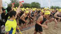 Country GM Herbalife Indonesia Andam Dewi membunyikan terompet tanda dimulainya Herbalife Bali International Triathlon 2016 di Sanur, Bali, Minggu (14/8). Sebanyak 1754 peserta dari 26 negara, ikut dalam lomba tersebut. (Liputan6.com/Made Anto)