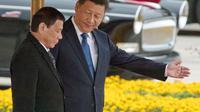 Presiden Filipona Rodrigo Duterte (kiir) berjalan berdampingan dengan Presiden China Xi Jinping (kanan) di Beijing. (AP/Ng Han Guan)