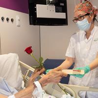 Seorang perawat memberikan buku dan bunga mawar kepada pasien yang dirawat di sebuah rumah sakit pada Hari Saint George di Barcelona, Spanyol (23/4/2020). (Xinhua/Francisco Avia)