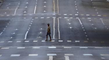 Seorang pria yang mengenakan masker berjalan di jalanan kosong saat penerapan jam malam di Havana, Kuba, Selasa (1/9/2020). Otoritas Kuba menerapkan lockdown selama 15 hari di Havana untuk keluar dari penularan COVID-19 tingkat rendah tetapi terus-menerus. (AP Photo/Ramon Espinosa)