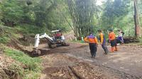 Tim BPBD Kota Batu membersihkan material sisa bencana tanah longsor yang sempat menutup akses jalan raya. Selama sepekan terakhir ini hampir tiap hari terjadi longsor di Kota Batu (BPBD Kota Batu)