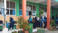 Para siswi SMPN 29 Makassar tampak mengenakan jilbab saat beraktifitas di sekolah (Liputan6.com/ Eka Hakim)