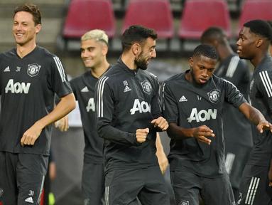 Pemain Manchester United, Bruno Fernandes bercanda dengan Aaron Wan-Bissaka saat sesi latihan jelang laga Liga Europa di Stadion Rhein Energie, Cologne, Minggu (9/8/2020). Manchester United akan berhadapan dengan Copenhagen. (AFP/Sascha Steinbach)