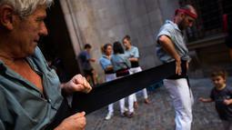 Dua Castellers bersiap-siap mengambil bagian dalam Castell di alun-alun Sant Jaume, Barcelona, Spanyol, Minggu (24/9). Dalam aksi ini, kelompok akar rumput telah membagikan satu juta kartu suara referendum kemerdekaan. (AP Photo/Emilio Morenatti)