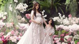Saat pemotretan foto maternity Magika, Nia Ramadhani mengenakan gaun yang sama dengan putri kesayangannya. Keduanya tampak memesona dengan tiara di kepala. Dengan desain gaun off-shoulder, Mikhayla terlihat super manis bak gulali. (Liputan6.com/Instagram/@ramadhaniabakrie)