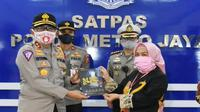 Deputi Pelayanan Publik Kementerian PAN-RB Diah Natalisa (kanan) memberikan buku Top 45 Pelayanan Publik kepada Kakorlantas Polri Irjen Istiono, saat mengunjungi Satpas SIM Polda Metro Jaya di Jalan Daan Mogot Raya, Jakarta, Kamis (4/6/2020). (Ist)