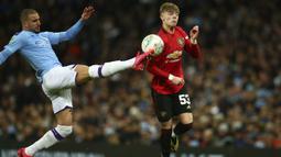 Bek Manchester City, Kyle Walker berebut bola dengan gelandang Manchester United, Brandon Williams pada pertandingan semifinal Piala Liga Inggris di stadion Etihad, Manchester, Rabu (29/1/2020). MU menang 1-0 atas City namun gagal ke final karena skor agregat 3-2. (AP Photo/Dave Thompson)