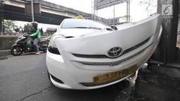 Kondisi taksi yang menabrak tiang di Jalan Ahmad Yani, Jakarta, Rabu (1/8). Mobil taksi berpelat nomor B 1121 BTD tersebut mengalami kerusakan parah pada bagian depan. (Merdeka.com/Iqbal Nugroho)