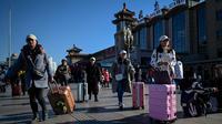Penumpang berjalan dengan membawa tas menuju pintu masuk stasiun kereta api Beijing di ibu kota China, Senin (21/1). Sebagian warga China yang tinggal di kota-kota besar mulai mudik untuk merayakan tahun baru Imlek bersama keluarga. (WANG ZHAO/AFP)