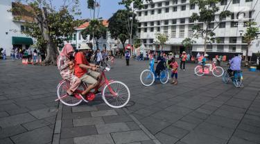 Pengunjung bersepeda mengelilingi kawasan Kota Tua, Jakarta, Sabtu (8/6/2019). Selama libur lebaran 2019, sejak 7 Juni kemarin hingga beberapa hari kedepan, jam berkunjung ke berbagai museum di kawasan wisata sejarah Kota Tua diperpanjang hingga pukul 20.00 WIB. (Liputan6.com/Faizal Fanani)