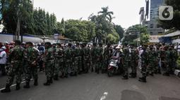 Prajurit TNI menghalau massa yang hendak menggelar demonstrasi 1812 di sekitar Istana Negara, Jakarta, Jumat (18/12/2020). Demo bertajuk Aksi 1812 ini selain menuntut pembebasan Rizieq Shihab, juga mendesak pengusutan kasus enam anggota FPI yang tewas tertembak polisi. (Liputan6.com/Johan Tallo)