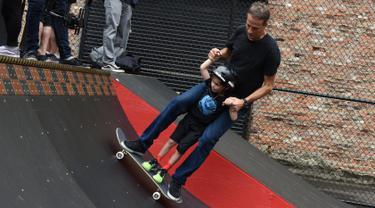 Legenda skateboard Tony Hawk bersama seorang anak Connor Curis meluncur dengan papan skateboard di Downtown Detroit (15/8). Taman skateboard ini  oleh Tony Hawk dan Ryan McGinness. (Tanya Moutzalias/Ann Arbor News-MLive.com Detroit via AP)