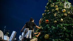 Pekerja menyelesaikan pembuatan Pohon Natal di Thamrin 10, Jakarta, Selasa (22/12/2020). Pemprov DKI mendirikan pohon Natal setinggi 12 meter di Thamrin 10 untuk memeriahkan suasana Natal. (Liputan6.com/Faizal Fanani)