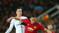 Gelandang Manchester United, Nemanja Matic berebut bola dengan pemain Paris Saint-Germain, Julian Draxler pada leg pertama 16 besar Liga Champions di Stadion Old Trafford, Selasa (12/2). Manchester United berhasil dikandaskan PSG, 0-2 (AP/Dave Thompson)