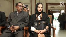 Aktris Nikita Mirzani (kanan) saat menjalani sidang isbat pernikahannya dengan Dipo Latief di Pengadilan Negeri Jakarta Selatan, Rabu (1/8). Nikita mengenakan gamis hitam dengan hijab warna senada. (Liputan6.com/Herman Zakharia)