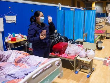 Pasien virus corona atau COVID-19 Ying (kiri) melambaikan tangan kepada petugas medis Cao Jinglei di sebuah rumah sakit sementara di Wuhan, China, Senin (9/3/2020). China menutup semua rumah sakit sementara yang dibuat untuk menangani virus corona di Kota Wuhan. (Xinhua/Shen Bohan)