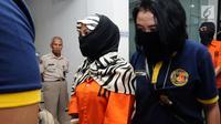 Salah satu tersangka kasus penyebaran ujaran bernada kebencian lewat internet digiring polisi usai rilis di Jakarta, Rabu (23/8). Tiga tersangka masuk dalam satu kelompok. (Liputan6.com/Helmi Fithriansyah)