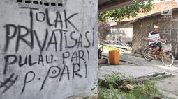 Wisatawan bersepeda melintasi coretan protes di salah satu tembok rumah di Pulau Pari, Kepulauan Seribu, Jakarta, Minggu (29/4). Coretan dibuat warga yang menolak klaim PT Bumi Pari Asri atas kepemilikan lahan Pulau Pari. (Merdeka.com/Iqbal S. Nugroho)
