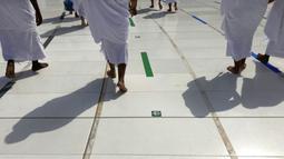 Umat muslim mengikuti tanda untuk memastikan jaga jarak untuk membantu menghentikan penyebaran virus corona COVID-19 saat mengelilingi Kakbah dalam pelaksanaan umrah di Masjidil Haram, Makkah, Arab Saudi, Minggu (30/5/2021). (AP Photo/Amr Nabil)