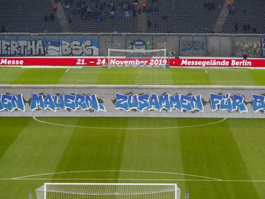 "Replika Tembok Berlin bertuliskan ""Bersatu menentang tembok.Bersatu untuk Berlin"" berdiri jelang pertandingan Hertha Berlin melawan RB Leipzig di Stadion Olimpiade, Berlin (9/11/2019). Replika Tembok Berlin berdiri untuk memperingati 30 tahun keruntuhan serta bersatunya Jerman. (AFP/Odd Andersen)"