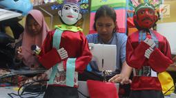 Perajin menyelesaikan pembuatan miniatur ondel-ondel di rumah produksi Kramat Jati, Jakarta, Senin (23/6/2019). Perajin bisa mengumpulkan omzet mencapai Rp 5 juta hingga Rp 8 juta per bulan. (merdeka.com/Arie Basuki)