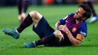 Megabintang Barcelona, Lionel Messi mengerang sambil memegangi sikut kanannya setelah mendarat tak sempurna saat terjatuh dalam lanjutan Liga Spanyol di Stadion Camp Nou, Minggu (21/10). Messi cedera saat Barca mengalahkan Sevilla. (AP/Manu Fernandez)