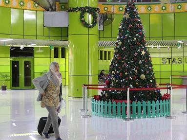 Penumpang melintas di dekat dekorasi pohon Natal di Stasiun Gambir, Jakarta, Jumat (21/12). Dekorasi tersebut dibuat untuk memercantik suasana Stasiun Gambir dalam rangka menyambut Hari Natal dan Tahun Baru 2019. (Liputan6.com/Immanuel Antonius)