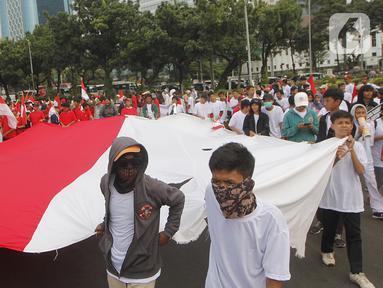 """Massa yang tergabung dalam Masyarakat Penegak Demokrasi (MPD) menggelar aksi damai """"Menyambut Pelantikan Presiden dan Wapres RI Terpilih"""" di Kawasan Patung Kuda, Jakarta, Kamis (10/10). Mereka mengimbau masyarakat menjaga situasi aman dan damai jangan terprovokasi. (Liputan6.com/Herman Zakharia)"""
