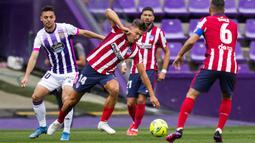 Pemain Atletico Madrid, Marcos Llorente, berebut bola dengan pemain Real Valladolid, Oscar Plano, pada laga Liga Spanyol di Stadion Jose Zorrilla, Sabtu (22/5/2021). Atletico Madrid menang dengan skor 2-1. (AP/Manu Fernandez)