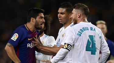 Striker Barcelona, Luis Suarez, bersitegang dengan bek Real Madrid, Sergio Ramos, pada laga La Liga Spanyol di Stadion Camp Nou, Barcelona, Minggu (6/5/2018). Kedua klub bermain imbang 2-2. (AFP/Josep Lago)