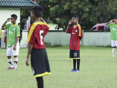 Para pemain SSB Maehanu dan SSB Persenal hormat bendera pada Liga Remaja UC News di Lapangan Masariku Yonif 733, Ambon, Selasa (28/11/2017). SSB Maehanu menang 1-1 (5-4) atas SSB Persenal. (Bola.com/Peksi Cahyo)