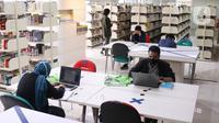 Pengunjung membaca buku di Perpustakaan Nasional (Perpusnas), Jakarta, Kamis (10/6/2020). Perpusnas membuka kembali membuka pelayanan mulai Kamis ini, 11 Juni 2020, dengan menyiapkan protokol kesehatan setelah beberapa bulan tutup akibat COVID-19. (Liputan6.com/Angga Yuniar)