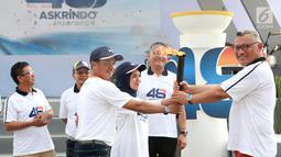"""Dirut PT Askrindo, Andrianto Wahyu Adi (kanan) menerima obor Torch Relay pada acara HUT ke-48 Askrindo di Ancol Fantastique, Jakarta, Sabtu (6/4). Kegiatan mengusung tema """"Satu Langkah Satu Tujuan Kita Tingkatkan Daya Saing Perusahaan"""". (Liputan6.com/HO/Iqbal)"""