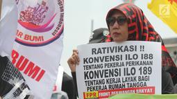 Massa yang tergabung dari berbagai elemen membawa poster saat melakukan aksi unjuk rasa memperingati Hari Buruh Migran Internasional 2018 di depan Istana Merdeka, Jakarta, Selasa (18/12). (Merdeka.com/Imam Buhori)