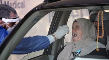 Petugas medis mengambil sampel usap (swab) COVID-19 dari seorang wanita di Rumah Sakit Khusus Universitas Ain Shams, Kairo, Mesir, Senin (13/7/2020). Hingga 13 Juli 2020, jumlah infeksi COVID-19 di Mesir terkonfirmasi telah mencapai angka 83.001 kasus. (Xinhua/Ahmed Gomaa)
