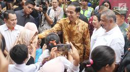 Presiden Jokowi bersalaman dengan warga saat menyaksikan pembagian paket Ramadan berupa sembako di Penjaringan, Jakarta, Selasa (13/6). Pembagian sembako ini merupakan inisiasi dari Kementerian BUMN dan perusahaan BUMN lainnya (Liputan6.com/Angga Yuniar)