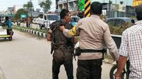 Pelaku suami bakar istri di Kota Dumai setelah diserahkan warga ke personel Polres Kota Dumai. (Liputan6.com/M Syukur)