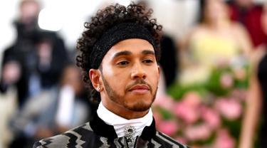 Pembalap Mercedes, Lewis Hamilton saat menghadiri Met Gala 2019 di Metropolitan Museum of Art di New York, AS (6/5/2019). Pria 34 asal Inggris ini tampil dengan jas hitam memamerkan desain zig-zag perak dan celana yang senada. (AP Photo/Charles Sykes)