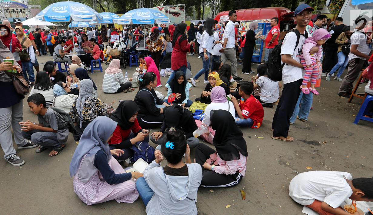 Pengunjung menikmati makan sambil lesehan jelang Closing Ceremony Asian Games 2018 di kawasan Gelora Bung Karno, Jakarta, Minggu (2/9). Mereka tidak mendapatkan kursi makan karena dipadati pengunjung. (Liputan6.com/Fery Pradolo)