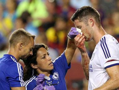 Pemain Chelsea Gary Cahill mendapatkan pengobatan dari tim medis akibat terluka karena duel udara saat mencetak gol pada Laga International Champions Cup di FedEx Field, AS, Rabu (29/7/2015) pagi WIB. (AFP Photo/Nicholas Kamm)