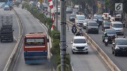 Pengguna kendaraan pribadi melintasi jalur bus Transjakarta di Jalan Otista Raya, Jakarta, Rabu (11/7). Pelanggaran lalu lintas ini dilakukan meski kondisi lalu lintas lancar. (Liputan6.com/Immanuel Antonius)