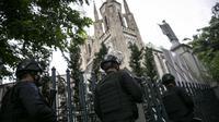 Personel kepolisian berjaga di depan Gereja Katedral, Jakarta, Kamis (1/4/2021). Sebanyak 150 personel gabungan TNI, Polri dan Satpol PP melakukan pengamanan jelang rangkaian perayaan Hari Paskah di gereja tersebut. (Liputan6.com/Faizal Fanani)