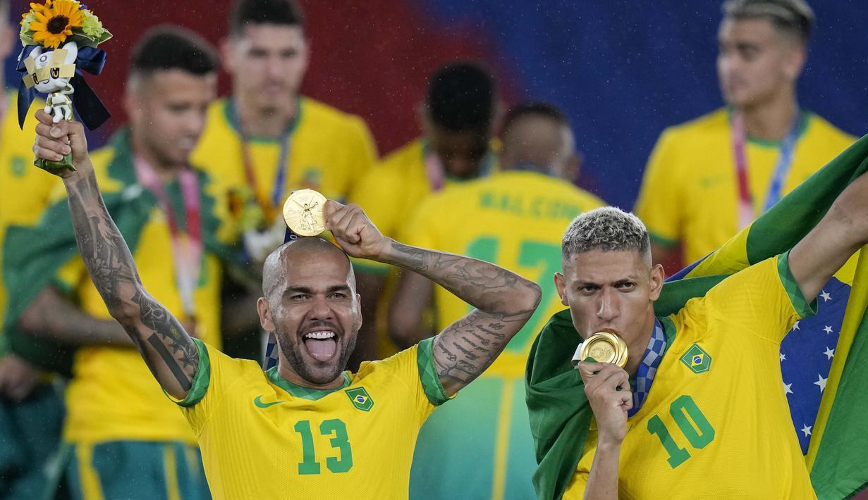 Dani Alves dan Richarlison berpose dengan medali emas Olimpiade Tokyo 2020. Bagi Brasil, ini adalah medali emas kedua di Olimpiade, setelah sebelumnya menjadi juara pada 2016 di Rio de Janeiro. (Foto: AP/Fernando Vergara)