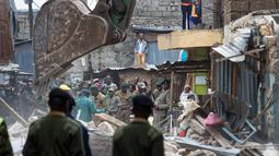 Petugas penyelamat menyisir puing bangunan lima lantai yang runtuh di daerah permukiman di ibu kota Kenya, Nairobi, Minggu (4/6). Diperkirakan puluhan orang masih belum ditemukan lantaran masih terjebak di antara reruntuhan. (AP Photo/Ben Curtis)
