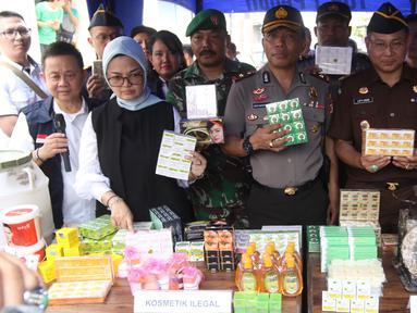 Kepala BPOM RI Penny K Lukito menunjukkan barang bukti kosmetik palsu di kawasan Tambora, Jakarta Barat, Selasa (15/5). Petugas menemukan 21 item produk jadi kosmetik ilegal, bahan baku, dan alat produksi. (Liputan6.com/Arya Manggala)
