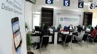 Petugas melayani warga yang mengurus iuran BPJS Kesehatan di Kantor BPJS Jalan Raya Pasar Minggu, Jakarta, Senin (4/11/2019). Perhimpunan Rumah Sakit Seluruh Indonesia memprediksi akan terjadi migrasi turun kelas pada peserta akibat kenaikan iuran 100 persen pada awal 2020. (merdeka.com/Arie Basuki)